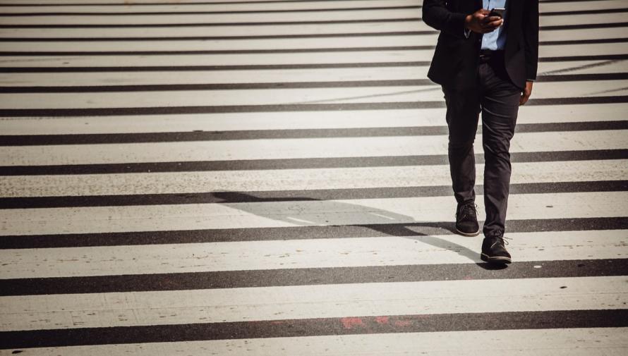 mężczyzna z telefonem komórkowym przechodzi przez przejście dla pieszych - Zdjęcie: Ketut Subiyanto / Pexels